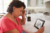 Senior Hispanic Woman At Home Looking At Old Photograph