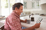 Senior Hispanic Man At Home Looking At Old Photograph
