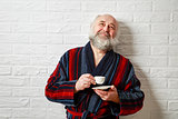 Happy Senior Man with Beard Drinking Coffee