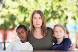 Serious mom sitting with sons at park table