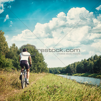Cyclist Riding a Bike on River Bank. Toned Photo.