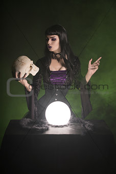 Beautiful witch holding human skull in her hand