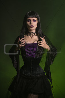 Beautiful witch dressed in a corset and velvet blouse