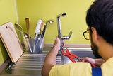 plumber installing, repairing water tap in kitchen
