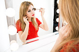 Beautiful Woman Applying Makeup at the Mirror