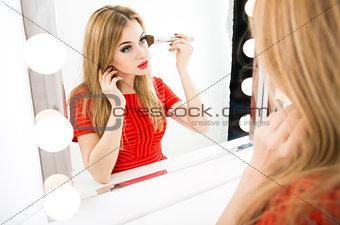 Beautiful Woman Applying Makeup at the Mirror