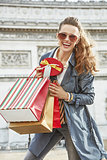 smiling trendy woman with shopping bags in Paris, France