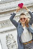 trendy woman near Arc de Triomphe showing red heart