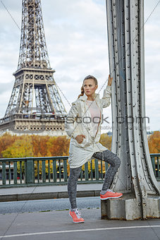 fit woman against Eiffel tower in Paris looking into distance