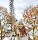 elegant woman in Paris, France taking selfie with phone