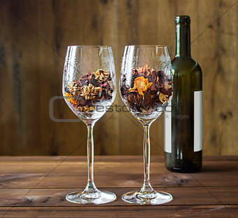 Autumn leaves in a wine glass and wine bottle on wooden table background