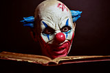 scary evil clown reading a book