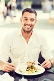 happy man eating salad for dinner at restaurant