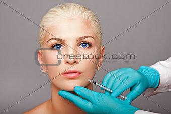 Cosmetic plastic surgeon injecting aesthetics face
