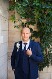 The groom in a blue suit with  vest