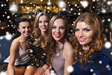 happy smiling women taking selfie at night club