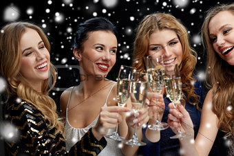 happy women clinking champagne glasses over black