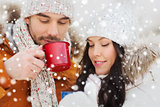 happy couple with tea cups over winter landscape
