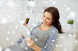 pregnant woman with tablet pc and credit card