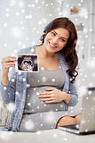 happy pregnant woman with ultrasound image at home