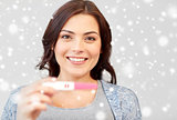 happy smiling woman holding home pregnancy test