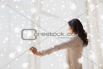 close up of pregnant woman opening window curtains