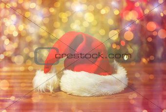 close up of santa hat on wooden table over lights