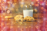 close up of cookies and milk over christmas lights