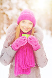 smiling young woman with cup in winter forest