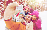 smiling friends with camera in winter forest