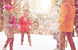happy friends playing with snow in winter forest