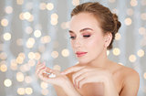 woman with moisturizing cream on hand over lights