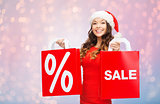 happy woman in santa hat with shopping bags