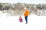happy father pulling sled with child in winter