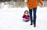 father pulling sled with happy child in winter