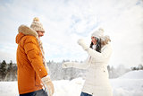 happy couple playing with snow in winter