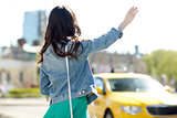 young woman or girl catching taxi on city street