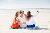 happy women taking selfie by smartphone on beach