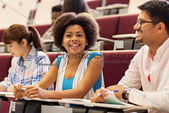 group of students with notebooks in lecture hall