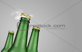 Three green beer bottles on grey background