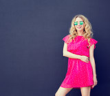 Summer Fashion Woman in Pink Dress at Dark Wall