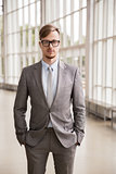 young businessman in suit and glasses at office