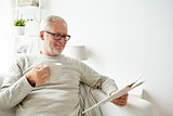 senior man in glasses reading newspaper at home