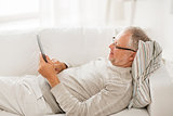 senior man with tablet pc lying on sofa at home