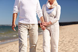 close up of senior couple walking on summer beach