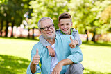 grandfather and boy showing thumbs up at summer