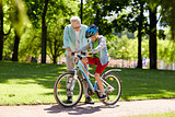 grandfather and boy with bicycle at summer park