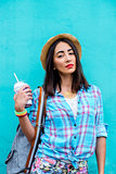 The girl in the city wearing shirt is holding a cocktail fresh  juice,  enjoying  backpack brunette, tanned, sensual make-up, recreation concept, travel, lifestyle. Summer day. Against the backdrop of  blue wall with red lipstick.