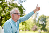happy senior man showing thumbs up at summer park