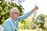 happy senior man showing thumbs up at summer park